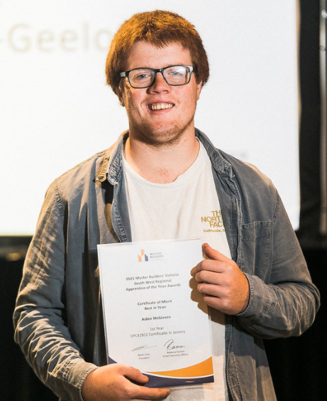 Young smiling red haired man in glasses with white t-shirt and grey shirt holding a certificate.
